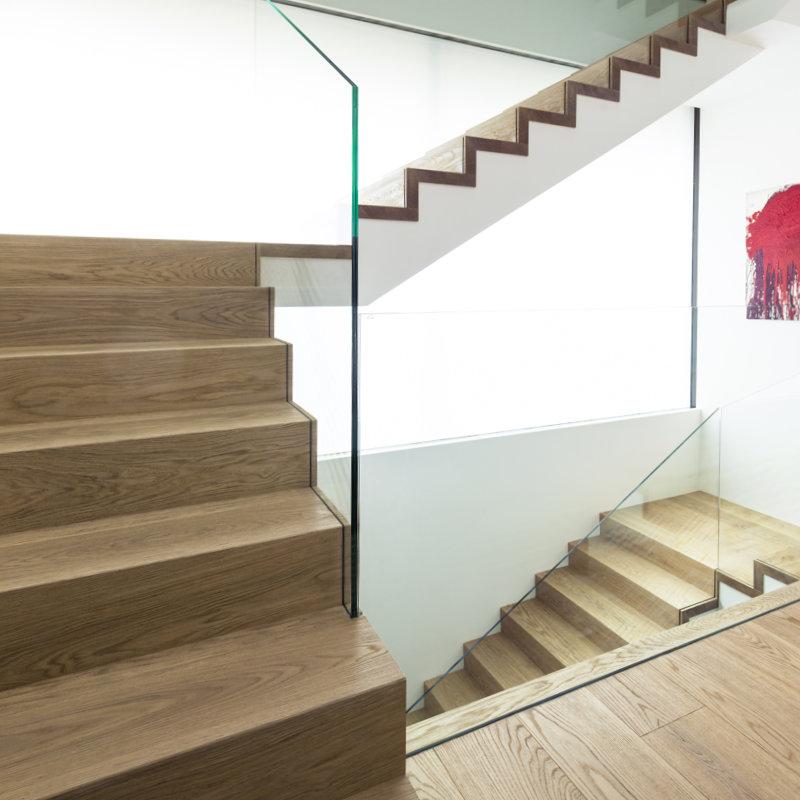 Referenzbild: Betonblocktreppe in Eiche mit Glasgeländer